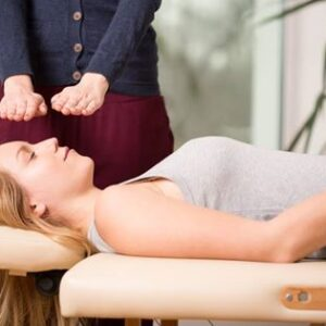 Person laying on a massage table with another person holding their hands above the first person's head, giving reiki